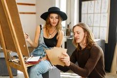 Künstler Consult sein Kollege beim Zeichnen lizenzfreies stockbild