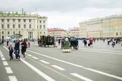 Künstler in den alten Kostümen unterhalten Touristen auf dem Palast-Quadrat in St Petersburg lizenzfreie stockfotos