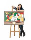 Künstler, der auf einem Gestell mit ihrer abstrakten Malerei sich lehnt Stockbild