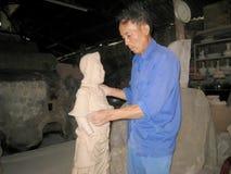 Künstler der Caytonwarendorf-Lehmstatue einer Gottheit Lizenzfreies Stockfoto