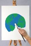 Künstler, der eine Abbildung der Erde auf einem Segeltuch malt Lizenzfreie Stockbilder