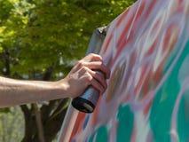Künstler, der Spraygraffiti-Farbendose im Freien malt Stockfotos