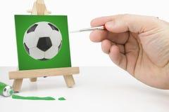 Künstler Easel mit einer grünen Segeltuchfußballmalerei und Künstler ha stockfotografie