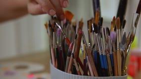 Künstler findet genauen Malerpinsel für ihr Kunstdesign stock video footage