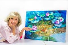 Künstler Gestures zu ihrer fertigen Malerei Lizenzfreies Stockfoto