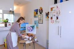 Künstler Girl Holds Brush in der Hand und zeichnet auf Segeltuch, aufhebt pH Lizenzfreies Stockbild