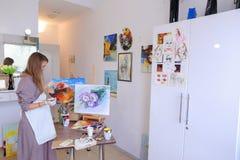 Künstler Girl Holds Brush in der Hand und zeichnet auf Segeltuch, aufhebt pH Lizenzfreie Stockfotografie