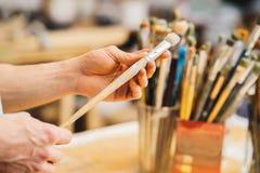Künstler hält die Bürste Malen Sie Bruses auf einem Unschärfehintergrund lizenzfreies stockbild