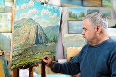 Künstler malt Ölgemälde mit einer Bürste und einer Palette stockfotografie
