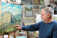 Künstler malt Ölgemälde mit einer Bürste und einer Palette lizenzfreie stockbilder