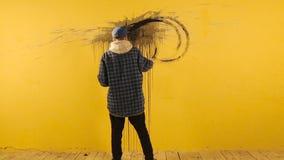 Künstler malt die abstrakte Verzierung mit schwarzer Bürste auf gelber Wand stock video