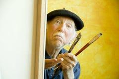 Künstler mit einem Barett an einem Segeltuch, das Baumuster betrachtet Stockfotografie