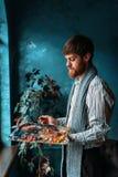Künstler mit Palette und Bürste vor Fenster Stockfoto