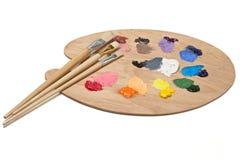 Künstler-Palette mit grundlegenden Farben und Pinseln Lizenzfreies Stockbild