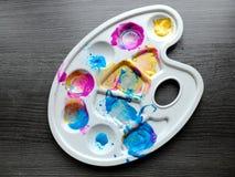 Künstler-Plastikpalette der Kinder mit verschiedenen Farbfarben auf grauem Hintergrund Konzept der Kunst mit Kindern, früh stockbilder
