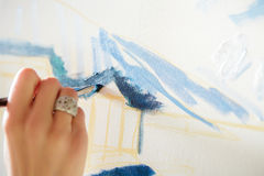 Künstler ` s Hand mit Bürstenmalerei auf Segeltuch Stockfotografie
