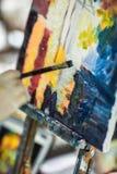 Künstler ` s Hand mit Bürstenmalerei auf Segeltuch Stockfotos
