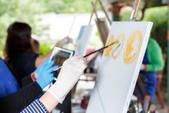 Künstler ` s Hand mit Bürstenmalerei auf Segeltuch Stockbild