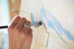 Künstler ` s Hand mit Bürstenmalerei auf Segeltuch Lizenzfreies Stockfoto