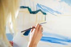 Künstler ` s Hand mit Bürstenmalerei auf Segeltuch Stockfoto