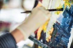 Künstler ` s Hand mit Bürstenmalerei auf Segeltuch Lizenzfreie Stockfotos