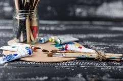 Künstler `s Werkstatt Einzelteile für Kind-` s Kreativität auf einem hölzernen Hintergrund Acrylfarbe und Bürsten auf weißem hölz Stockbild