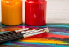 Künstler `s Werkstatt Segeltuch, Farbe, Bürsten, Palettenmesser, das auf dem Tisch liegt Kunstwerkzeuge Künstlerarbeitsplatzhinte Stockbild
