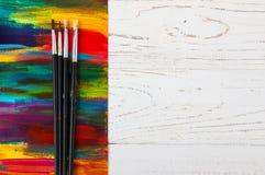 Künstler `s Werkstatt Segeltuch, Farbe, Bürsten, Palettenmesser, das auf dem Tisch liegt Kunstwerkzeuge Künstlerarbeitsplatzhinte Stockfotografie