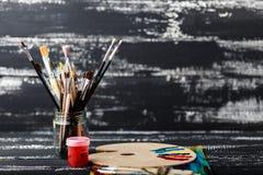 Künstler `s Werkstatt Segeltuch, Farbe, Bürsten, Palettenmesser, das auf dem Tisch liegt Kunstwerkzeuge Künstlerarbeitsplatzhinte Stockfotos