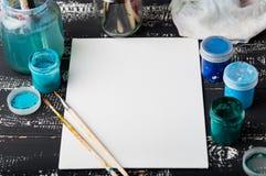 Künstler `s Werkstatt Segeltuch, Farbe, Bürsten, Palettenmesser, das auf dem Tisch liegt Kunstwerkzeuge Künstlerarbeitsplatzhinte Lizenzfreie Stockfotografie