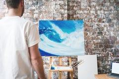 Künstler steht vor dem Gestell mit einem Segeltuch und betrachtet seine Arbeit stockfoto