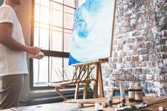 Künstler steht vor dem Gestell mit einem Segeltuch und betrachtet seine Arbeit Maler im Kunststudio Hobby und kreativer Besetzung lizenzfreie stockfotografie