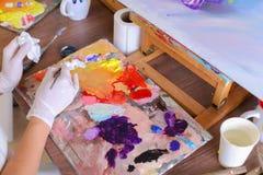 Künstler verdrängt Farbe von den Rohren auf Palette für mischende Farben t Lizenzfreie Stockbilder