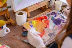 Künstler verdrängt Farbe von den Rohren auf Palette für mischende Farben t Lizenzfreies Stockbild