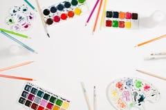 Künstlerarbeitsplatz mit Aquarell, Farbbleistiften, Palette und Bürsten am weißen Hintergrund Flache Lage, Draufsicht Lizenzfreie Stockfotos