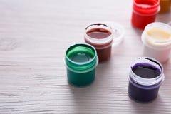 Künstlerarbeitsplatz, Satz Farbfarben auf hölzernem Schreibtisch Stockbild