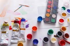 Künstlerarbeitsplatz, Satz Farbfarben auf hölzernem Schreibtisch Stockfotografie