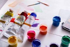 Künstlerarbeitsplatz, Satz Farbfarben auf hölzernem Schreibtisch Stockbilder