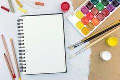 Künstlerarbeitswerkzeuge auf Tabelle: Aquarell, Malerpinsel und Bleistifte Stockfotografie