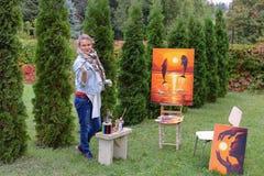 Künstlerfrau hält Malerei und betrachtet sie und wirft an der Kamera auf lizenzfreie stockbilder