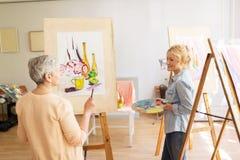 Künstlerfrauen mit den Gestellen, die an der Kunstakademie malen Lizenzfreies Stockfoto