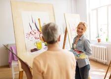 Künstlerfrauen mit den Gestellen, die an der Kunstakademie malen Lizenzfreie Stockfotos