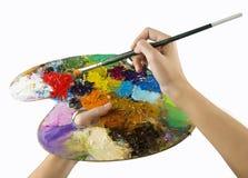 Künstlerhände, die einen Pinsel und eine Palette halten Stockbild