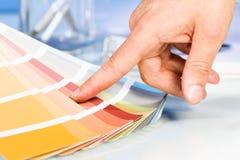 Künstlerhand, die mit dem Finger auf Farbproben in der Palette zeigt Stockbild