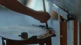 Künstlerhand mischt Ölfarben auf der Palette vor Malerei stock footage