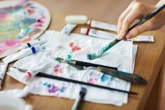 Künstlerhand mit Malerpinsel-, Papier- und Farbenrohren lizenzfreie stockfotos