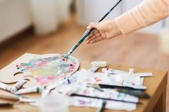 Künstlerhand mit Malerpinsel und Farbpalette lizenzfreie stockfotografie