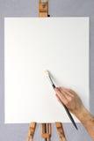 Künstlerholdingpinsel auf unbelegtem Segeltuch Stockbild
