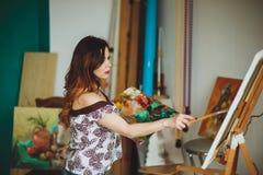 Künstlerin, die ein Bild in einem Studio malt stockbild