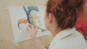 Künstlerin, die ein Bild im Studio bei der Unterhaltung am Telefon malt Stockfotos